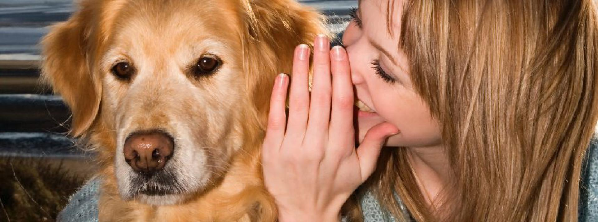 Young Woman Whispering into Dog's Ear