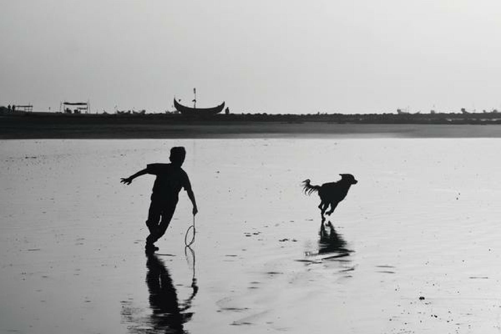 19 Mar 2010, Bangladesh, Bengal --- A child is chasing a dog on the sea beach of Saint Martin's Island, Bangladesh --- Image by © Mohammad Moniruzzaman/Corbis